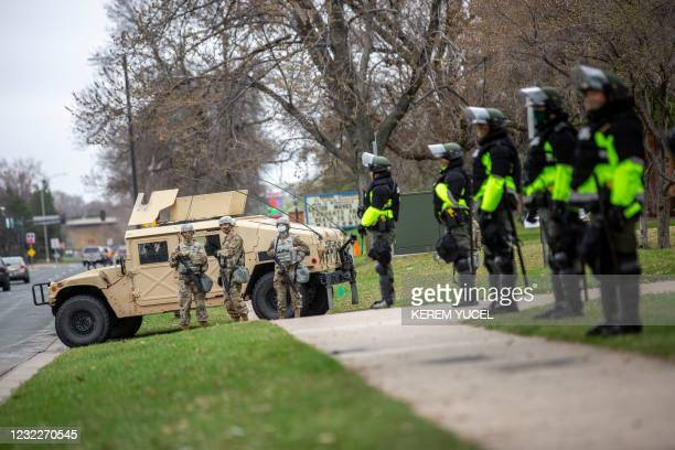 Minnesota National Guard and law enforcement members stand guard outside the Brooklyn Center Police Station after a police officer shot and killed a...