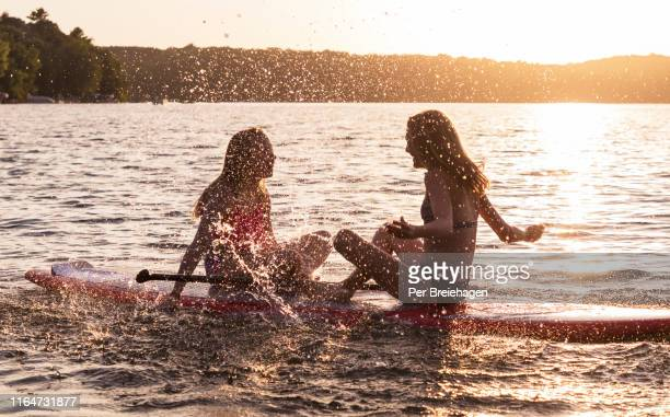 two girls splashing each other on a paddleboard, minnesota - paddleboard stock photos and pictures