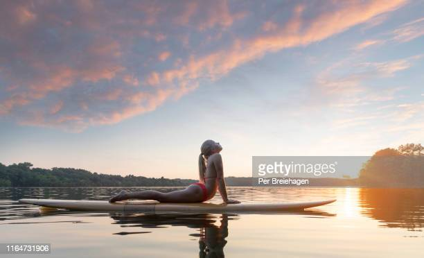 a girl doing yoga on a paddleboard in a lake, minnesota - paddleboard stock photos and pictures