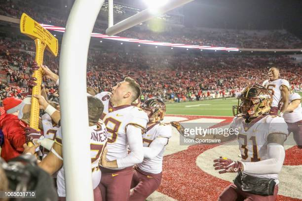 Minnesota Players celebrate with the Paul Bunyan axe following their win over Wisconsin in a college football game between the University of...