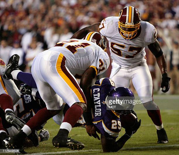 Minnesota running back Chester Taylor gets past Washington defenders Sean Taylor and Warrick Holdman to score a touchdown in the first quarter of...