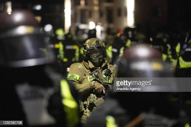 Minnesota State Trooper stands behind other troopers as he holds a rifle as protests over police killing of Daunte Wright continue in Brooklyn...