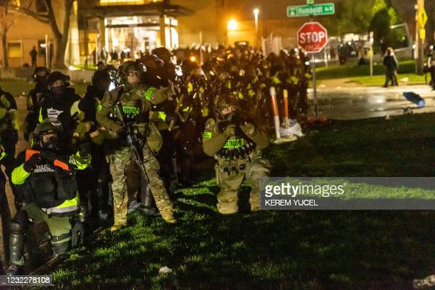 Minnesota State Troopers prepare to fire tear gas at protesters as they stand guard outside the Brooklyn Center police station after a police officer...