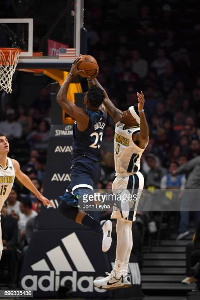 Minnesota Timberwolves guard Jimmy Butler goes up for a shot past Denver Nuggets guard Torrey Craig during the first quarter on December 20 2017 in...