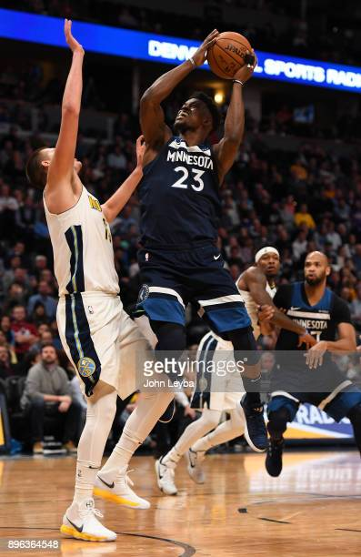 Minnesota Timberwolves guard Jimmy Butler takes a shot over Denver Nuggets center Nikola Jokic during the fourth quarter on December 20 2017 in...