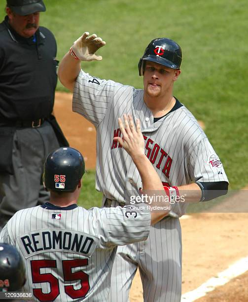 """Minnesota Twins' 1st Baseman, Justin Morneau, gets """"high fives"""" from teammates after hitting a 2-run homer during the game against the Chicago White..."""