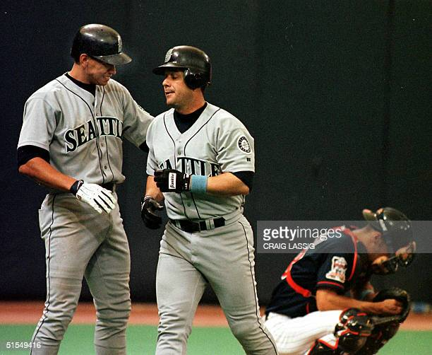 Minnesota Twins catcher Corey Koskie hangs his head as Seattle Mariners Alex Rodriguez congratulates Edgar Martinez on his two run homer in the 6th...