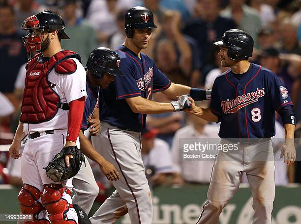 Minnesota Twins catcher Joe Mauer is congratulated at the plate by Minnesota Twins second baseman Jamey Carroll after his three run home run in the...