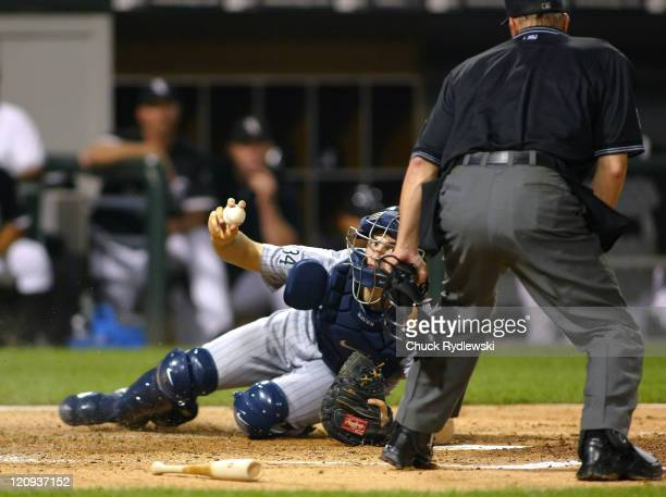 Minnesota Twins' catcher Joe Mauer shows Home Plate Umpire Jeff Kellogg the ball after tagging out Ross Gload during their game against the Chicago...