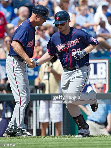 Minnesota Twins' Chris Parmelee is congratulated by third base coach Steve Liddle after hitting a solo home run in the second inning during Sunday's...