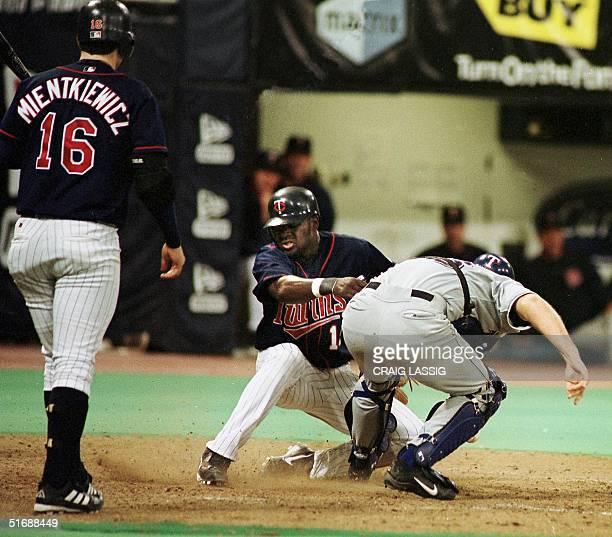Minnesota Twins Cristian Guzman steals home past Texas Rangers catcher Bill Haselman after a wild pitch by Rangers pitcher Hideki Irabu to bring the...