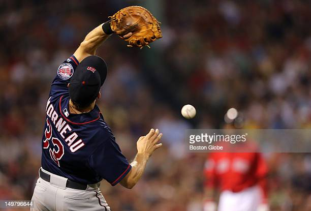 Minnesota Twins first baseman Justin Morneau misplayed the catch of a pop foul ball hit by Boston Red Sox left fielder Carl Crawford background at...