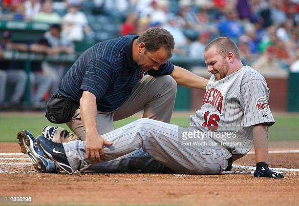Minnesota Twins' Jason Kubel grimaces in pain after a foul tip bounced off his leg during his at bat in the first inning of a baseball game against...