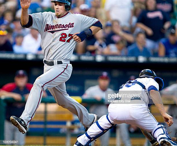 Minnesota Twins' JJ Hardy leaps onto home plate ahead of the tag from Kansas City Royals catcher Jason Kendall on a tworun single by Joe Mauer in the...
