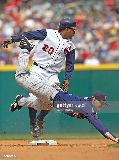 Minnesota Twins' Nick Punto dives for the ball thrown by third baseman Michael Cuddyer as Cleveland Indians' Ronnie Belliard steps onto second base...