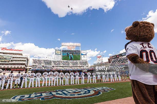 Minnesota Twins players and mascot TC Bear look on during the national anthem as 2 F16s flyover before the Minnesota Twins home opener at Target...