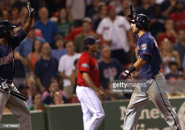 Minnesota Twins right fielder Darin Mastroianni is congratulated at the plate after scoring the game winning run in the tenth inning off Boston Red...