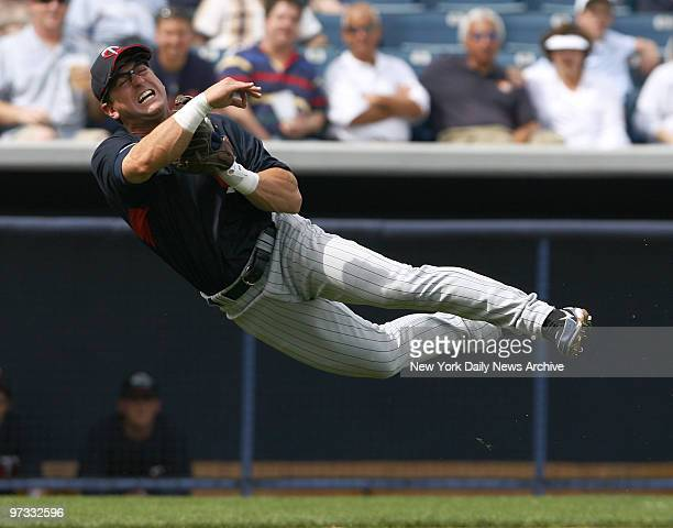 Minnesota Twins' third baseman Nick Punto attempts to make the out with a throw to first during a spring training game against the New York Yankees...
