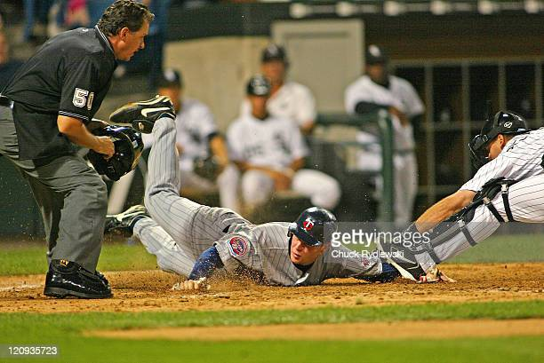 Minnesota Twins'1st Baseman, Justin Morneau, evades A.J. Pierzynski's tag and scores the Twins' 2nd run during the game against the Chicago White Sox...