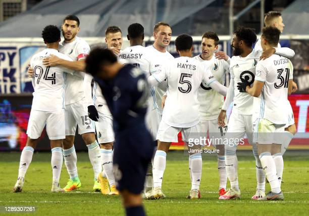 Minnesota United players congratulate each other after defeating Sporting Kansas City 3-0 to win the MLS playoff game at Children's Mercy Park on...