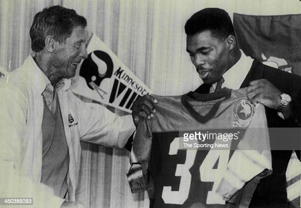 Minnesota Vikings coach Jerry Burns greets Herschel Walker of the Minnesota Vikings as Walker holds up his Vikings' jersey during a 1989 press...