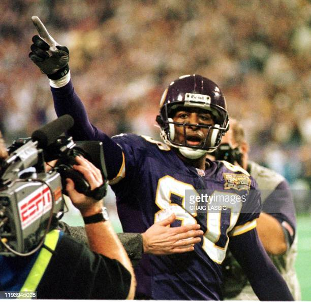 Minnesota Vikings Cris Carter gestures to the crowd after scoring a touchdown and completing his 1000th reception against the Detroit Lions in the...