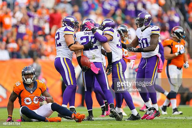 Minnesota Vikings players celebrate with free safety Harrison Smith after he intercepted a pass intended for wide receiver Demaryius Thomas of the...