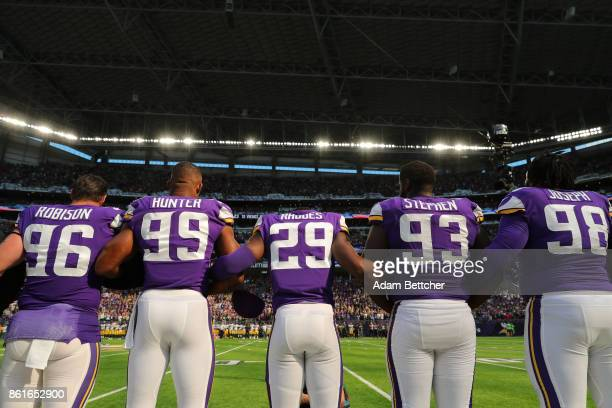 Minnesota Vikings players lock arms during the national anthem before a game against the Green Bay Packers on October 15, 2017 at US Bank Stadium in...
