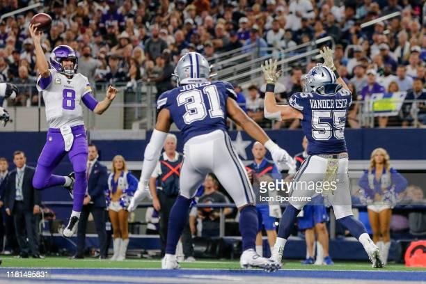 Minnesota Vikings quarterback Kirk Cousins jumps up to pass the football over Dallas Cowboys outside linebacker Leighton Vander Esch and cornerback...