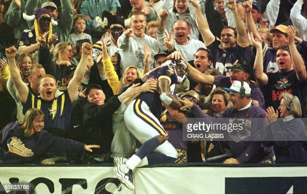 Minnesota Vikings' Randy Moss celebrates with the crowd after scoring a touchdown on a long pass from Randall Cunningham early in the fourth quarter...