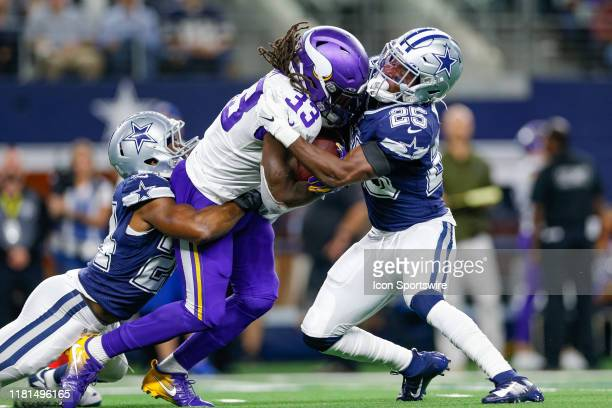 Minnesota Vikings Running Back Dalvin Cook drags Dallas Cowboys Cornerback Chidobe Awuzie while colliding with Safety Xavier Woods during the game...