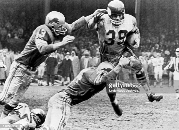 Minnesota Vikings running back Hugh McElhenny leaps but cannot avoid being tackled by Detroit Lions players Gary Lowe and Dick LeBeau during a...