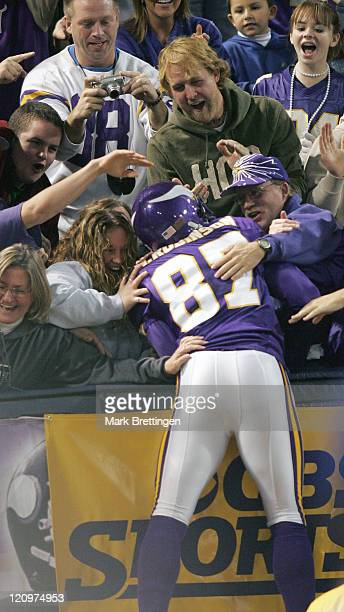 Minnesota Vikings wide receiver Marcus Robinson celebrates his third touchdown pass with the fans in the stands during a game against the Cleveland...