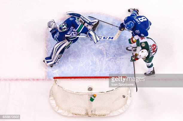 Minnesota Wild Center Mikko Koivu scores a goal on Goalie Ryan Miller as Vancouver Canucks Defenceman Chris Tanev defends against Minnesota Wild Left...