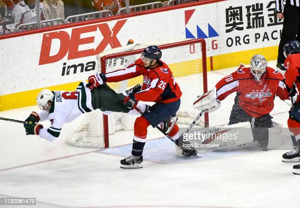 Minnesota Wild center Ryan Donato collides with Washington Capitals goaltender Braden Holtby who makes the save as he is pushed by center Nic Dowd in...