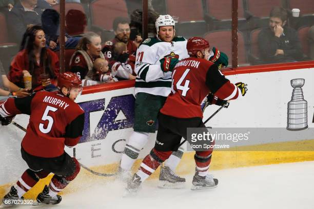 Minnesota Wild center Ryan White is checked by Arizona Coyotes defenseman Kevin Connauton during the NHL hockey game between the Minnesota Wild and...