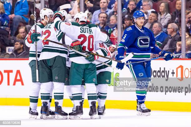 Minnesota Wild congratulate Left Wing Zach Parise after he scored a goal as Vancouver Canucks Defenceman Chris Tanev skates by during their NHL game...