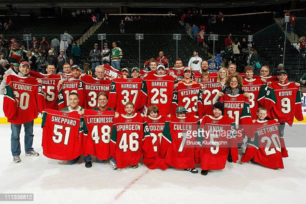 """Minnesota Wild fans hold up jerseys they received from the """"jerseys off our backs"""" promotion after the game against the Edmonton Oilers at Xcel..."""