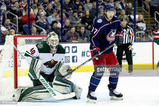 Minnesota Wild goaltender Devan Dubnyk focuses on the puck while Columbus Blue Jackets right wing Josh Anderson attempts to block his view in the...