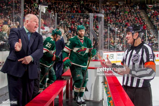Minnesota Wild head coach Bruce Boudreau and referee Brad Watson talk during the game against the Nashville Predators at the Xcel Energy Center on...