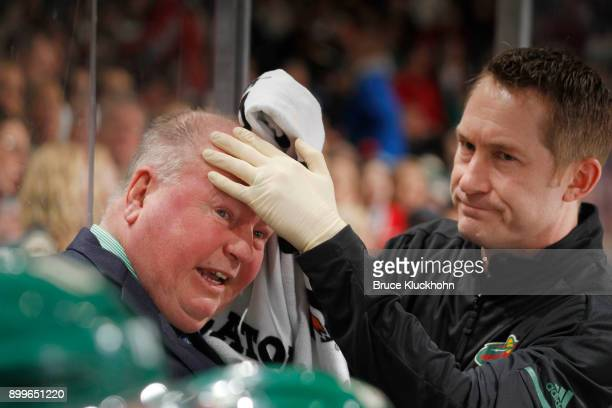 Minnesota Wild head coach Bruce Boudreau is treated by a member of the training team after being struck by a puck during the game against the...