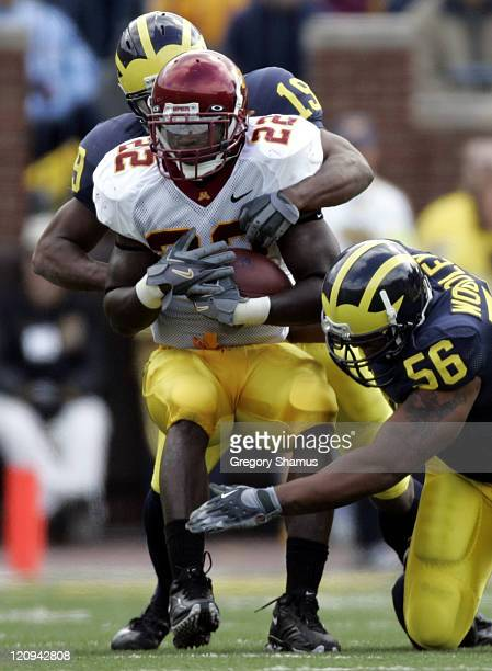 Minnesota's Laurence Maroney gets tackled by Michigan's LaMarr Woodley and Willis Barringer at Michigan Stadium on October 8 2005 in Ann Arbor...