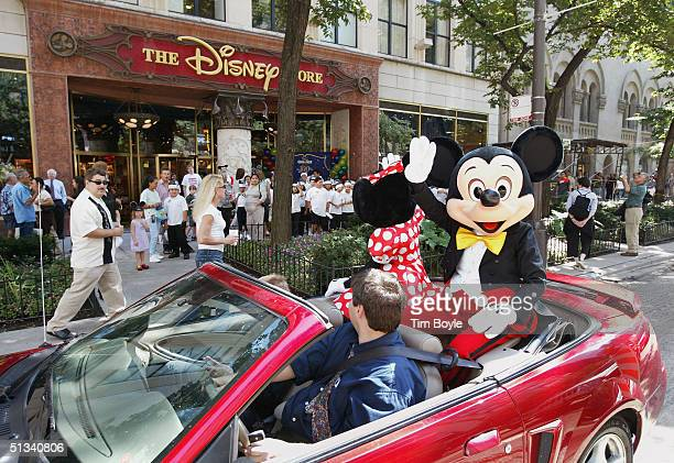 Minnie and Mickey Mouse drive past the Disney Store as they wave to Mickey Mouse Club theme singing contest participants September 23 2004 in Chicago...