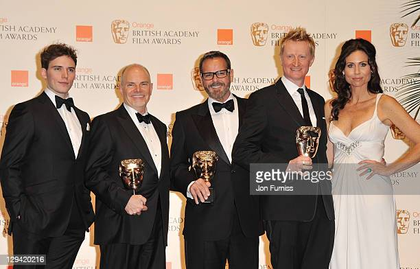 Minnie Driver and Sam Claflin pose with Guy Hendrix Dyas Larry Dias and Doug Mowat the winners of the Production design award for 'Inception' during...