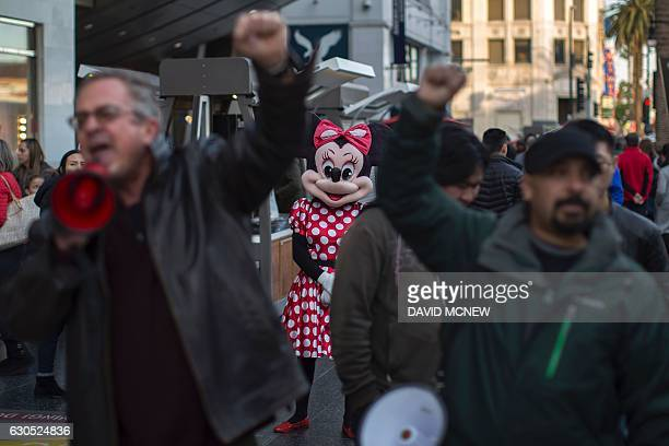 A Minnie Mouse character looks on as people protest at the Hollywood Walk of Fame star for Donald Trump in reaction to a Twitter post by US...