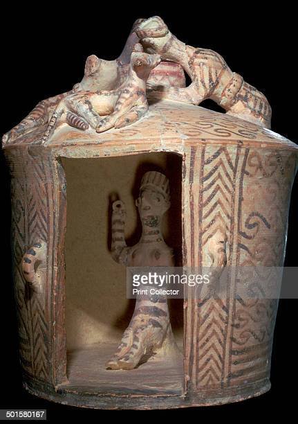 Minoan pottery shrine containing a goddess with raised arms On the roof two human figures watch the goddess through the lightwell From the Giamalakis...