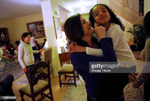 Minoo Panahi holds her niece Isabelle Placide during a Baha'i devotional in the home of a family member January 11 2013 in Northbrook Illinois