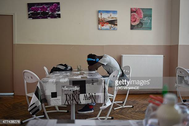 A minor child placed in a CEF sits in the dining hall of a center on June 16 2015 in SaintBricesousForet Created in 2002 those centers are...