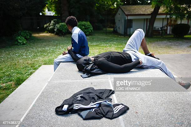 Minor children placed in a CEF sit on a table-tennis table in front of the center, on June 16, 2015 in Saint-Brice-sous-Foret. Created in 2002, those...
