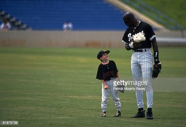 Minor League Baseball Basketball player Birmingham Barons Michael Jordan on field with child fan Seth Garrett during anthem before game Birmingham AL...